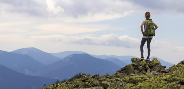 Chica en la cima de una montaña que está orgullosa por organizar viajes en grupo inolvidables.