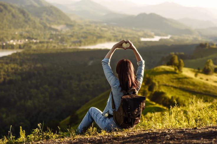 Imagen que muestra a una chica en la cima de una montaña haciendo un corazón con las manos. Y la primera clave antes de comenzar con las 3 estrategias de diferenciación, es contar los viajes desde el corazón.