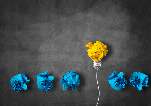 Creatividades de papel donde existe una de color amarillo mejorada y que destaca de las demás que son todas azules y peores. Viene a decir que para avanzar en la búsqueda de tu cliente ideal, debes estudiar a la competencia para superarla.