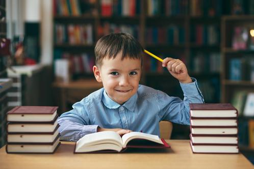 Niño de unos 9 años en la biblioteca poniendo en orden sus ideas para acabar con el caos y convertirlo en claridad con el fin de crear una oferta irresistible para su cliente ideal.