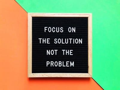 Pizarra con letras en inglés que viene a decirte que pongas foco en la solución y no en el problema para encontrar a tu cliente ideal.